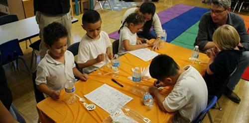 five children doing crafts around a table