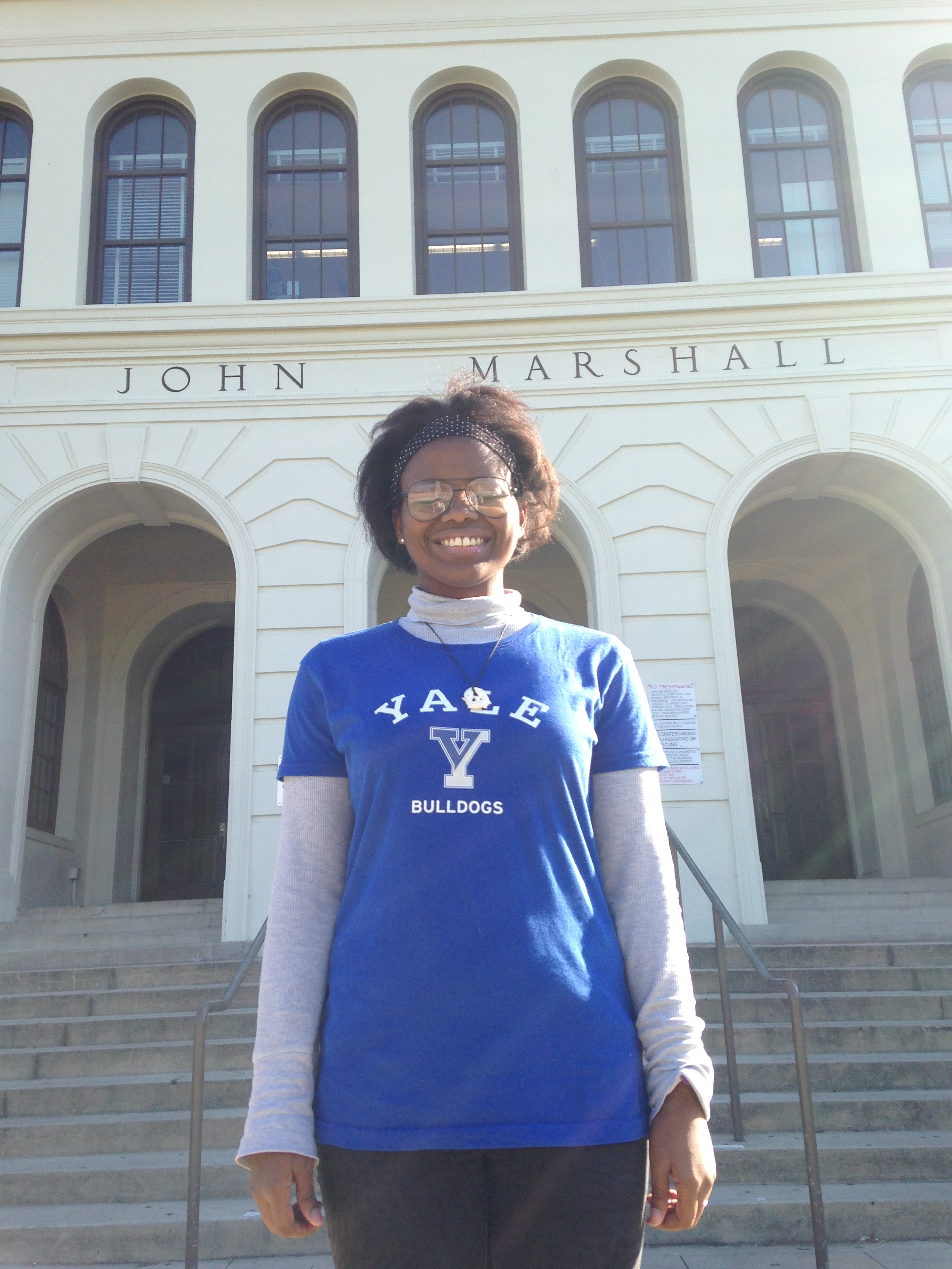 Photo of student wearing a blue shirt in front of the school entrance