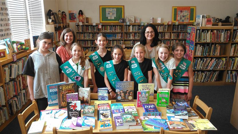 Girl Scout Troop 147-1 with Library Coordinator, Principal, and books they helped library purchase.