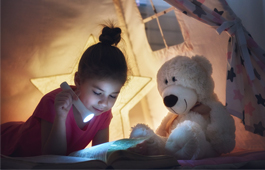 Girl reading a book with a flashlight in a tent with teddy bear
