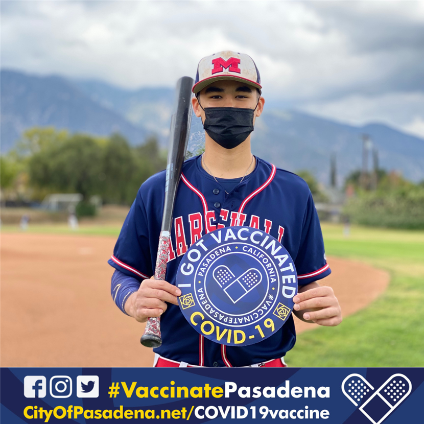 Photo of baseball player holding I got vaccinated sign