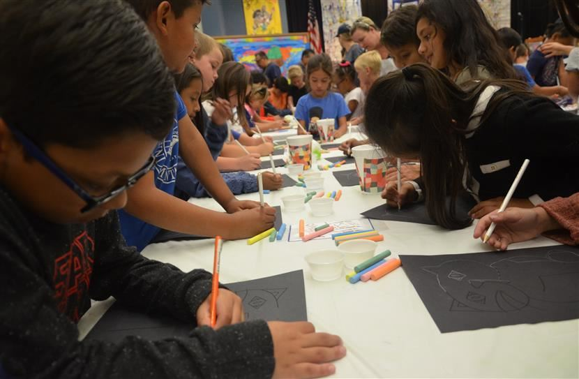 A picture of elementary students at table drawing with chalk