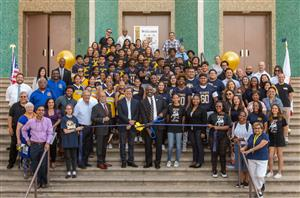 A photo of a group of students, faculty, and officials at a ribbon cutting ceremony.