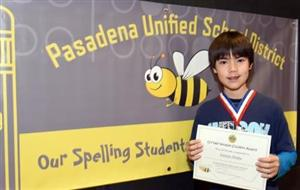 Child holding a Spelling Bee award